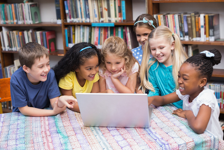 Cute pupils looking at laptop in libraryの写真素材 [FYI00003181]