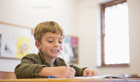 Happy pupil writing in notepad at his deskの写真素材 [FYI00003194]