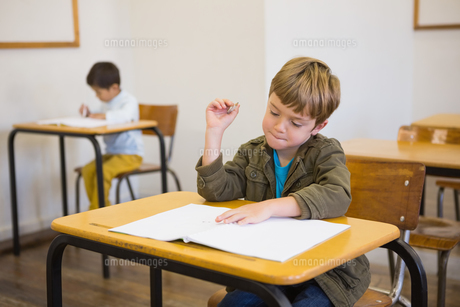 Pupil writing in notepad at his deskの写真素材 [FYI00003196]