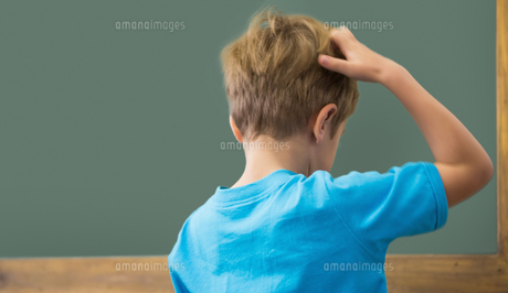 Thinking pupil scratching his head in classroomの写真素材 [FYI00003202]