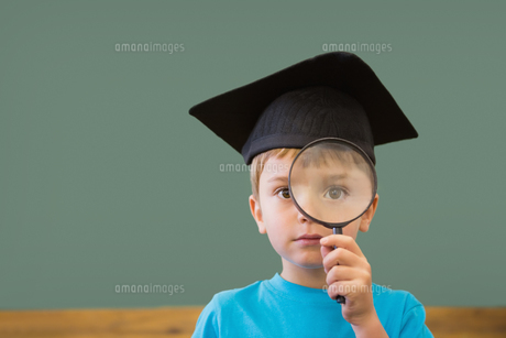 Cute pupil in mortar board smiling at camera in classroomの写真素材 [FYI00003205]