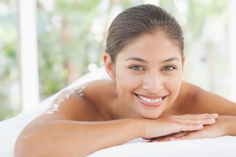 Beautiful brunette lying on massage table with salt scrub on backの写真素材 [FYI00003239]