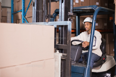 Forklift driver operating machine with boxes on itの写真素材 [FYI00003253]