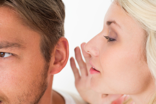 Woman whispering secret into a mans earの写真素材 [FYI00003258]