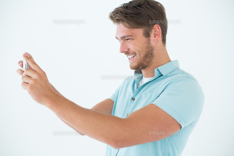 Happy man looking at his mobile phoneの写真素材 [FYI00003263]