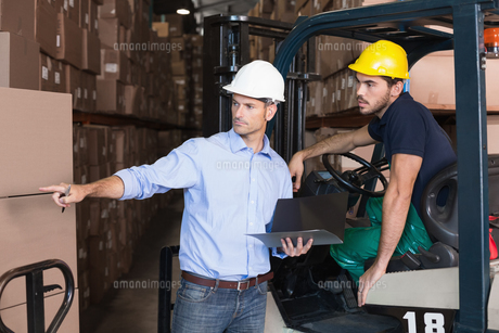 Warehouse manager talking with forklift driverの写真素材 [FYI00003271]
