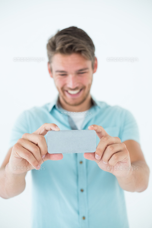 Happy young man looking at his mobile phoneの写真素材 [FYI00003272]