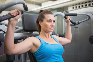 Fit brunette using weights machine for armsの写真素材 [FYI00003276]