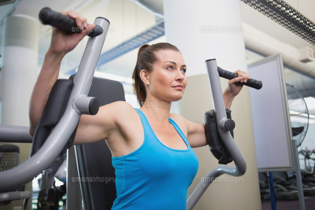 Fit brunette using weights machine for armsの写真素材 [FYI00003277]