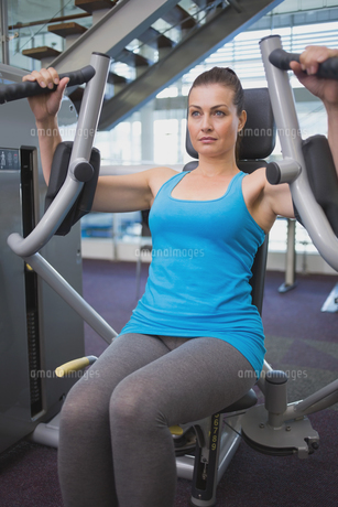 Fit brunette using weights machine for armsの写真素材 [FYI00003278]