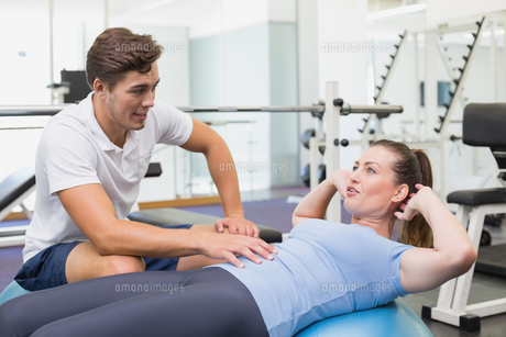 Personal trainer working with client on exercise ballの写真素材 [FYI00003280]