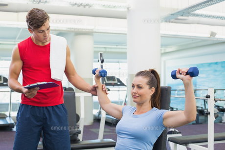 Personal trainer helping client lift dumbbellsの写真素材 [FYI00003281]