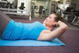 Fit brunette doing sit ups on exercise matの写真素材 [FYI00003283]