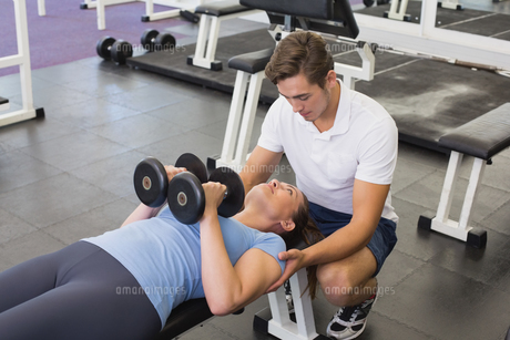 Personal trainer helping client lift dumbbellsの写真素材 [FYI00003285]