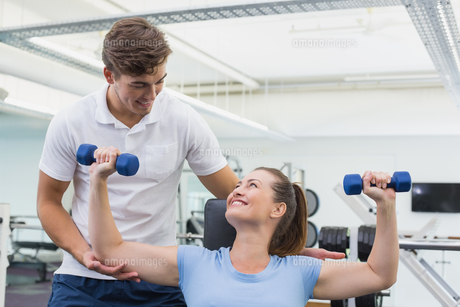 Personal trainer helping client lift dumbbellの写真素材 [FYI00003286]