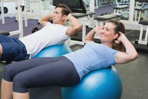 Couple doing sit ups on exercise ballsの写真素材 [FYI00003287]