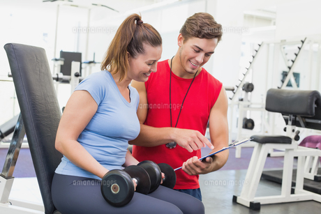 Personal trainer working with client holding dumbbellの写真素材 [FYI00003290]