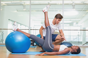 Personal trainer working with client using exercise ballの写真素材 [FYI00003291]