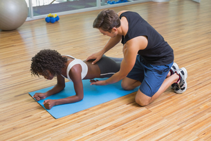 Personal trainer working with client on exercise matの写真素材 [FYI00003293]