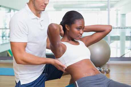 Personal trainer working with client on exercise ballの写真素材 [FYI00003295]