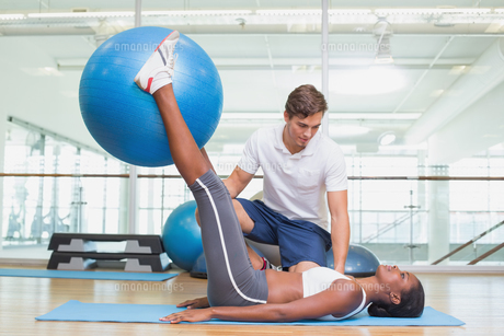 Personal trainer working with client holding exercise ballの写真素材 [FYI00003296]