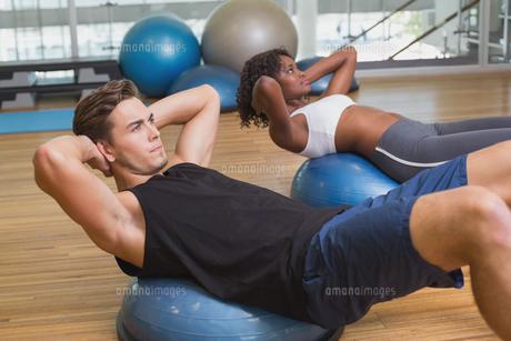 Couple doing sit ups on exercise ballsの素材 [FYI00003302]