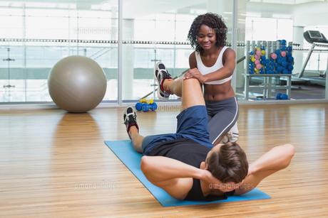 Personal trainer working with client on exercise matの写真素材 [FYI00003305]