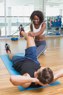 Personal trainer working with client on exercise matの写真素材 [FYI00003306]