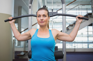 Fit brunette using weights machine for armsの写真素材 [FYI00003310]