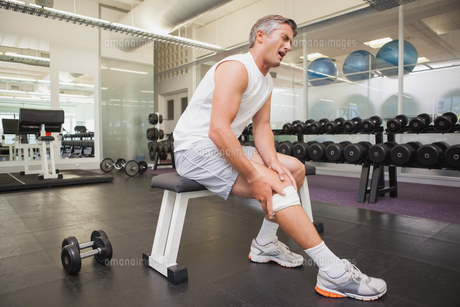 Injured man gripping his knee in the weights roomの写真素材 [FYI00003313]