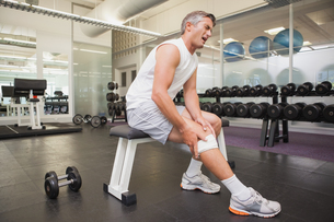 Injured man gripping his knee in the weights roomの素材 [FYI00003313]