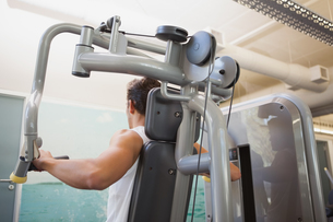 Fit man using weights machine for armsの素材 [FYI00003319]