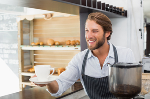 Handsome barista offering a cup of coffeeの写真素材 [FYI00003322]