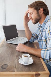 Casual man using laptop having coffeeの写真素材 [FYI00003339]