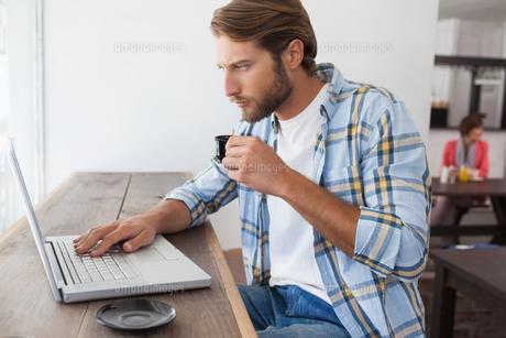 Casual man using laptop drinking espressoの写真素材 [FYI00003340]