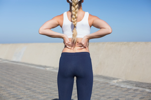 Fit blonde touching her back on the pierの写真素材 [FYI00003353]