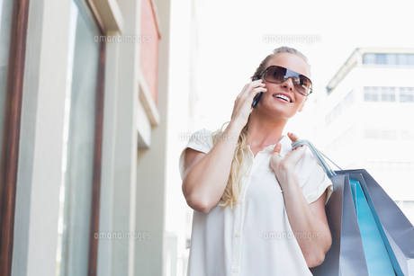 Pretty blonde making a call holding shopping bagsの写真素材 [FYI00003382]