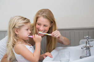 Happy mother and daughter brushing their teethの写真素材 [FYI00003417]