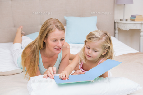 Cute little girl and mother on bed readingの写真素材 [FYI00003421]