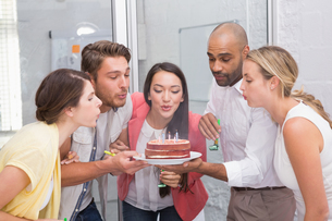 Businesswoman blowing the candles on her birthday cakeの写真素材 [FYI00003440]