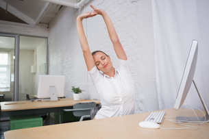 Businesswoman stretching hands in officeの写真素材 [FYI00003442]