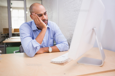 Tired businessman using computer at deskの写真素材 [FYI00003443]