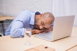 Businessman sleeping by laptop at deskの写真素材 [FYI00003444]