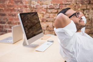Businessman with hands behind head in officeの写真素材 [FYI00003446]