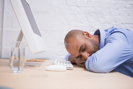 Businessman sleeping by computer at deskの素材 [FYI00003449]