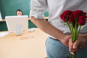 Man hiding bouquet in front of businesswoman at deskの写真素材 [FYI00003453]