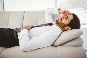 Sick businessman lying on the couchの写真素材 [FYI00003463]