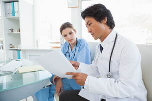 Doctor and surgeon reading notesの写真素材 [FYI00003472]