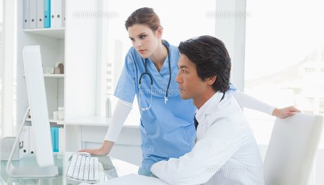 Doctor and surgeon looking at a computerの写真素材 [FYI00003475]