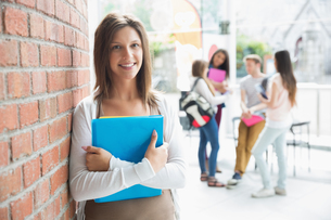 Pretty student smiling and holding notepadsの写真素材 [FYI00003486]